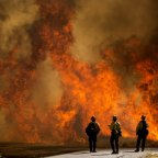 Firefighters watch as flames flare at the Apple Fire in Cherry Valley, California.