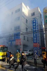 Firefighters work as smoke billows from a hospital in Miryang, South Korea