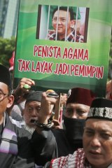 Muslims protesters hold up a poster depicting Jakarta Governor 'Ahok' behind bars.