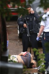A police officer stands guard over an injured Ahmad Khan Rahami before he was taken away from the scene of a shootout with police on Monday.