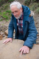 Dr Tom Rich reveals a dinosaur footprint at Melanesia Beach.