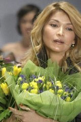 Gulnara Karimova holds flowers at the end of a parade.