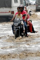 A motor-cyclist and his passengers travel along a water-logged road as the first monsoon rains arrive in Jalandhar on June 7, 2012.  The monsoon rains brought relief from the scorching heat wave.