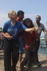 Asylum seekers are helped to shore.