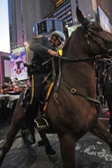Mounted police prevent Occupy Wall Street demonstrators from breaking through a barricade in New York's Times Square.