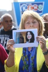 A marcher holds an image of Jill Meagher.