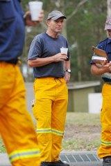 Volunteer … opposition leader, Tony Abbott, listens to a bushfire briefing.