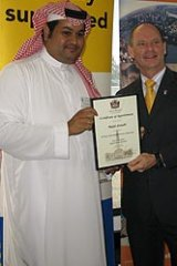 UQ computer engineering PhD student Majid Alotaibi of Saudi Arabia, in traditional clothing, receives his certificate from Lord Mayor Campbell Newman.