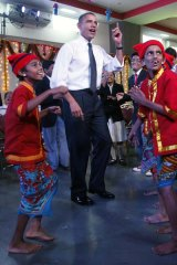 Getting into the local rhythm ... Barack Obama and Michelle Obama dance with children during a visit to the Holy Name High School in Mumbai.