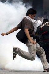 A demonstrator in Kuala Lumpur tries to kick away a tear-gas canister.