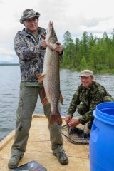 Russian President Vladimir Putin shows a big pike he caught while fishing during a mini-break in the Siberian Tyva region, Russia.