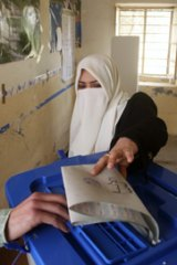 A resident casts her vote at a polling station in Falluja in Iraq's parliamentary election.