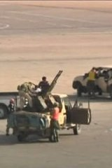 Armed militia in military pick-up vehicles on the tarmac of Tripoli international airport.