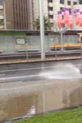 Splash ... Drivers try to get through flooding at the Domain Interchange.