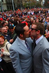 Damien Stevens (left) and Chris Todd celebrate their unofficial marriage with thousands in Spring Street.