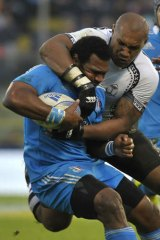 Italy's Manoa Vosawai is grabbed by Fiji's Nemani Nadolo.