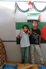 Ashjan, 9, and Marwan, 11, stand in front of a Palestinian flag in a cubicle at a camp for Syrian-based Palestinian refugees near the Turkish-Syrian border.