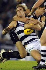 Collingwood's Cameron Wood grabs Joel Selwood in a high tackle.