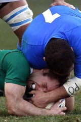 Cian Healy of Ireland  is tackled by Salvatore Perugini.