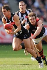 Luke Ball is chased by Essendon's Jobe Watson at the MCG.