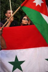 Protesters wave Jordanian and Syrian national flags aoutside the Friends of Syria conference, in Amman, Jordan, Wednesday, May 22, 2013.