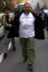 Artist Ai Weiwei reveals a shirt with his portrait as he walks into the government tax office last week.