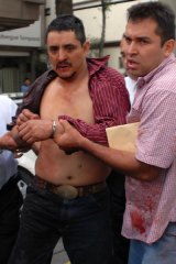 Luis Felipe Hernandez Castillo (left) is arrested by Mexican police after a shooting at Mexico City's subway,