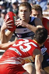 Geelong's Joel Selwood evades Gold Coast's Michael Rischitelli (front) and Jared Brennan at Skilled Stadium.