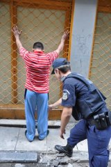 Greek tragedy ... An Athenian policeman checks a foreigner for ID papers.