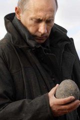 Russian Prime Minister Vladimir Putin holds an artefact at a research station at the mouth of the Lena River.