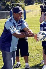 Passing tips . . . New York Yankees star Curtis Granderson, watched by Prime Minister John Key's son Max, throws around a rugby ball at a Blues training session.