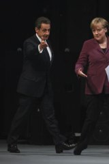 Angela Merkel and Nicolas Sarkozy arrive for a news conference ahead of the Group of 20 Summit  in Cannes.