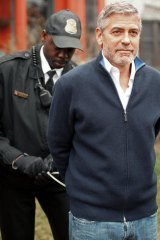 George Clooney is handcuffed by a member of the US Secret Service.