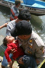 A police officer carries an unconscious child who was on the boat that capsized late on Tuesday after hitting a reef off the coast of Sukapura, in West Java.