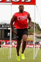 Jamaican Asafa Powell reaches for his hamstring after his Stawell Gift heat.