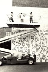 Haring painting the mural in 1984.