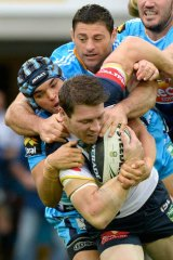 Under pressure: Rory Kostjasyn of the Cowboys is tackled  by a pack of Titans players.