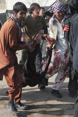 Afghans remove bodies and help the wounded after the suicide bombing at the Abul Fazl Shrine  in Kabul.
