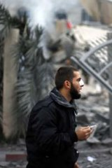 Aftermath ... a wounded Hamas policeman guards the destroyed headquarters of Ismail Haniyeh in Gaza City.