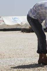 A Syrian refugee bathes his child at Al Zaatri refugee camp.