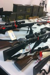 Police seized 13 firearms, nearly $18,000 in cash and several thousand rounds of ammunition in a raid on a Port Kennedy home over the weekend.