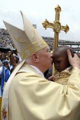 Isolated ... Pope Benedict XVI kisses a young girl as he leaves the Amadou Ahidjo stadium in Cameroon.
