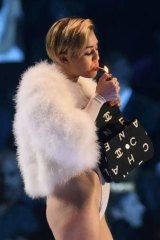 Singer Miley Cyrus smokes on stage after receiving the Best Video award during the 2013 MTV Europe Music Awards.