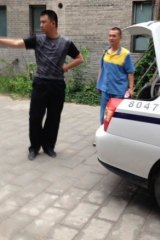 Detained: Australian artist Guo Jian, seen here in the yellow and blue uniform of a detainee, is escorted from his Beijing home by Chinese police after returning there briefly on Friday, June 6.