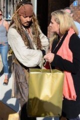Redlands mayor Karen Williams presents Johnny Depp with a parting gift of local wares.