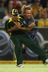 Forgettable night ... Khalid Latif is tackled by a spectator.
