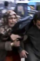Air strike ... a man is helped from the bakery bombing.
