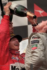 Michael Schumacher pours champagne on the winner of the 1997 Australian Grand Prix, David Coulthard.