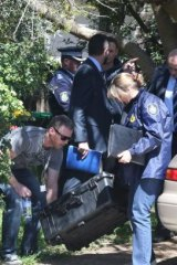 Police leave with what appears to be a sword after a raid in Sydney on Thursday.