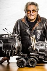 George Miller shows models of vehicles in <i>Fury Road</i>.
